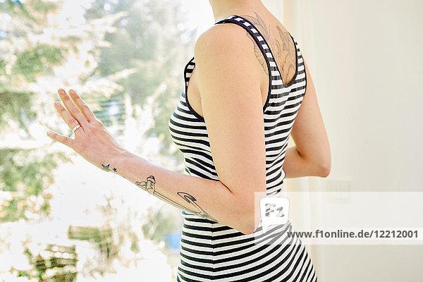 Mittlere erwachsene Frau  mit Tätowierungen auf dem Arm  aus dem Fenster schauend  Mittelteil