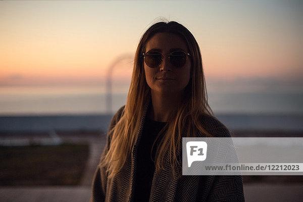 Porträt einer Frau im Schatten mit Sonnenbrille  die lächelnd in die Kamera schaut Porträt einer Frau im Schatten mit Sonnenbrille, die lächelnd in die Kamera schaut