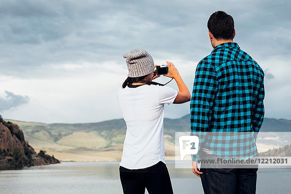 Couple beside Dillon Reservoir  taking photograph  rear view  Silverthorne  Colorado  USA
