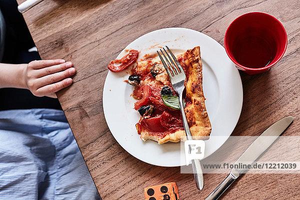 Pizzaschnitte auf weißem Teller  Kinderhand auf dem Tisch  Mittelteil  Ansicht von oben
