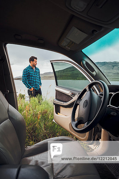 Mid adult man standing beside Dillon Reservoir  view through parked car  Silverthorne  Colorado  USA