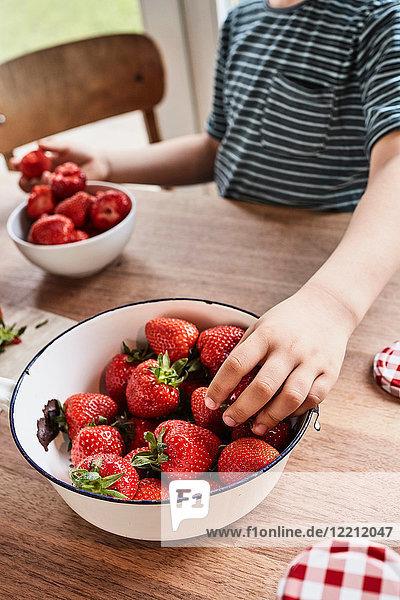 Junge nimmt Erdbeere aus Schale  Mittelteil  Nahaufnahme