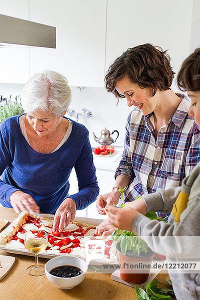 Junge  Mutter und Großmutter backen gemeinsam Pizza in der Küche