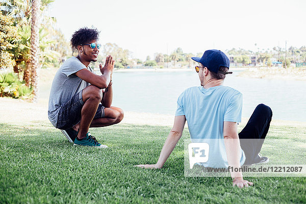 Friends relaxing on grass by lake  Long Beach  California  US