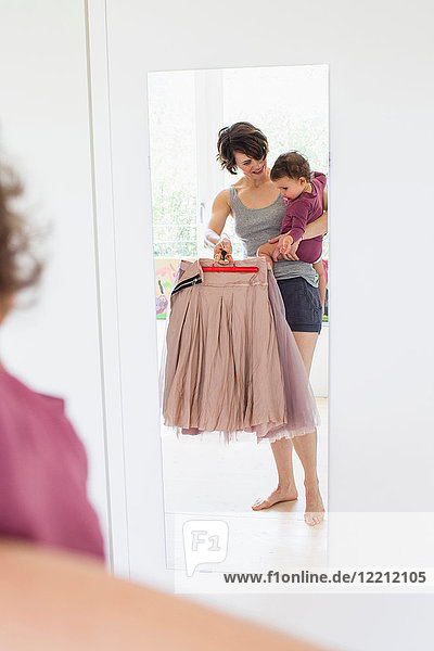 Mutter hält Baby Tochter  hält verschiedene Outfits in der Hand