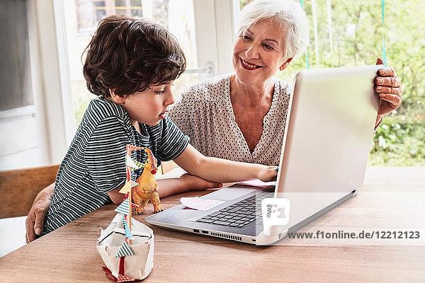 Großmutter und Enkel am Tisch sitzend  mit Laptop