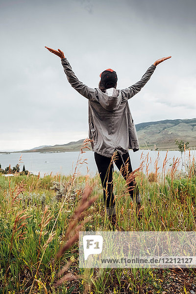 Young woman standing near Dillon Reservoir  arms raised  rear view  Silverthorne  Colorado  USA