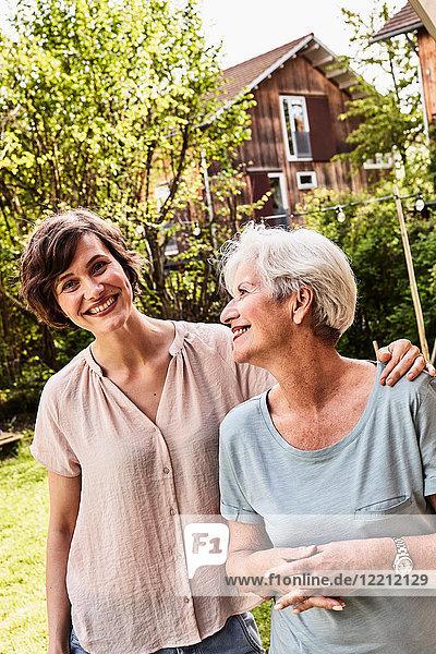 Porträt einer älteren Frau mit erwachsener Tochter  im Freien  lächelnd
