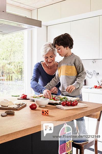 Großmutter und Enkel  die zusammen Pizza machen