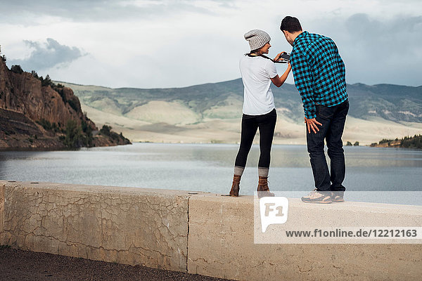 Couple standing on wall beside Dillon Reservoir  looking at camera  rear view  Silverthorne  Colorado  USA