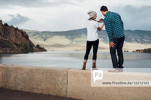 Ehepaar steht an der Wand neben dem Dillon-Stausee und schaut in die Kamera  Rückansicht  Silverthorne  Colorado  USA