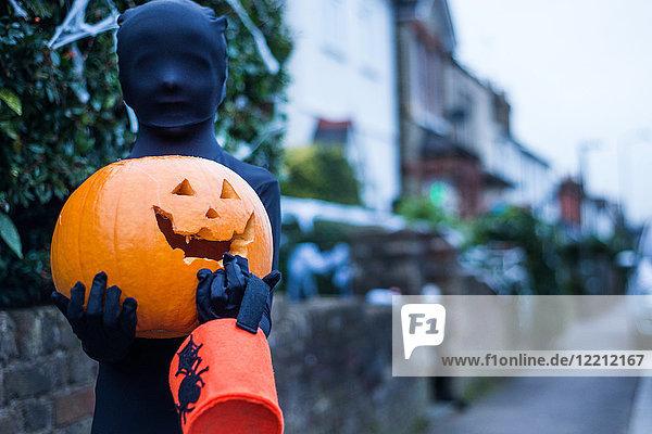 Porträt eines Jungen in Halloween-Kostüm  der einen Kürbis und einen Eimer mit Süßem oder Sauberem hält