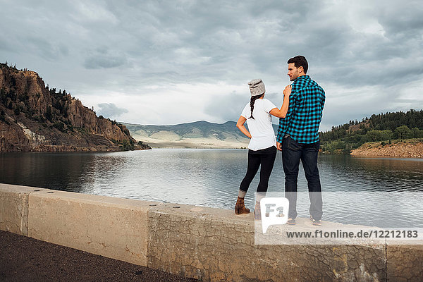 Couple standing on wall beside Dillon Reservoir  looking at view  rear view  Silverthorne  Colorado  USA