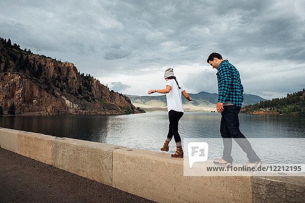 Couple walking along wall beside Dillon Reservoir  Silverthorne  Colorado  USA