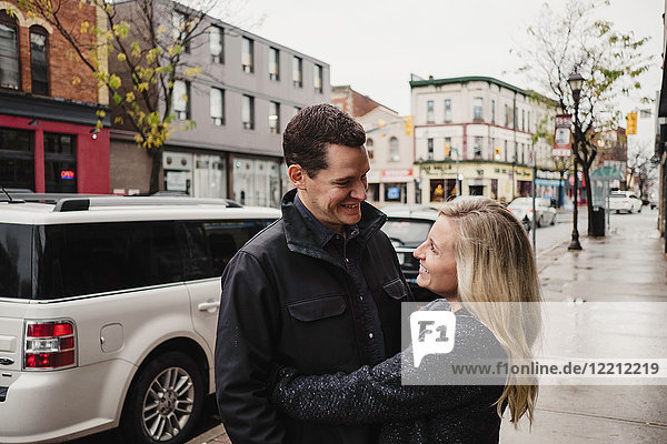 Mid adult couple hugging in street  smiling
