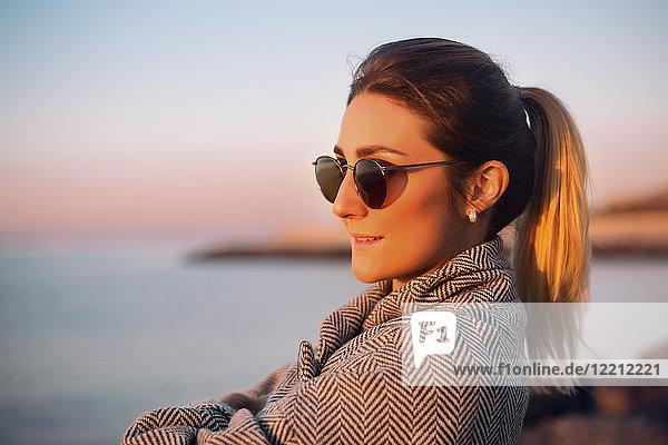 Porträt einer Frau mit Pferdeschwanz und Sonnenbrille  die lächelnd wegschaut  Odessa  Odeska Oblast  Ukraine  Osteuropa
