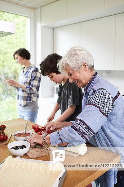Großmutter und Enkel bereiten das Essen in der Küche zu  Mutter im Hintergrund