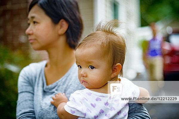 Mittlere erwachsene Frau  die ihre Tochter auf dem Arm trägt
