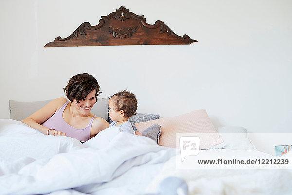 Mutter sitzt mit Mädchen im Bett und lächelt