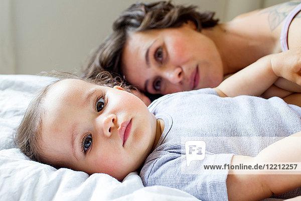 Porträt von Mutter und kleiner Tochter  die sich auf dem Bett entspannen