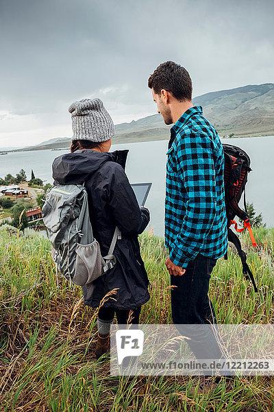 Couple standing beside Dillon Reservoir  using digital tablet  Silverthorne  Colorado  USA