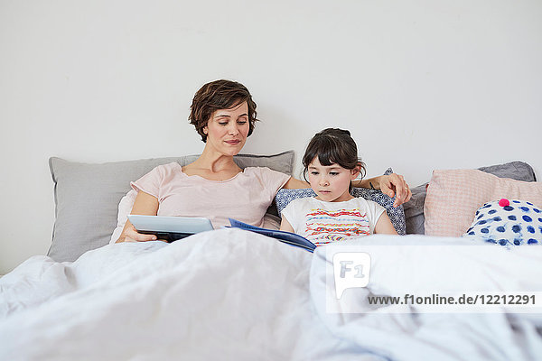 Mutter und Tochter entspannen sich im Bett  Tochter liest Buch  Mutter hält digitales Tablett