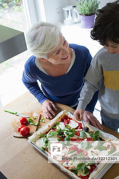 Großmutter und Enkel machen zusammen Pizza
