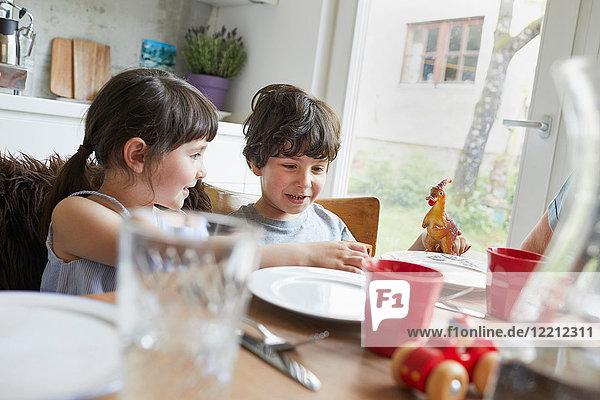 Junge und Mädchen sitzen am Esstisch und lächeln