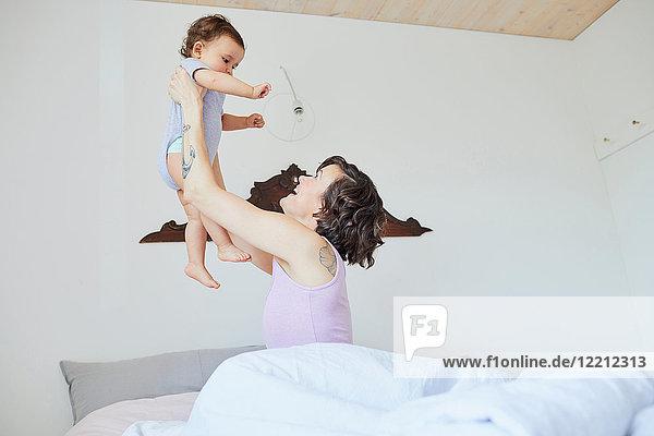 Mutter sitzt im Bett  hält das Mädchen in der Luft und lächelt