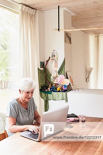 Ältere Frau am Tisch sitzend  mit Laptop