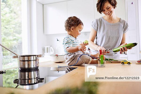 Kleines Mädchen sitzt auf der Küchentheke und sieht der Mutter beim Gurkenschneiden zu