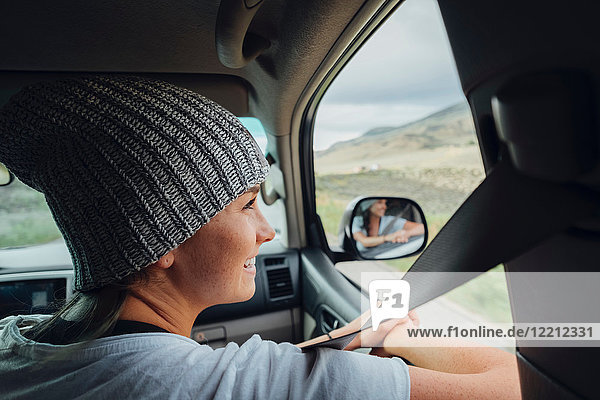 Young woman sitting in car  looking at view out of car window  Silverthorne  Colorado  USA