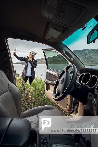 Young woman standing beside Dillon Reservoir  holding smartphone  view through parked car  Silverthorne  Colorado  USA