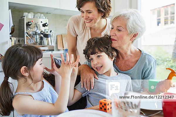 Junges Mädchen beim Fotografieren  Bruder  Mutter und Großmutter  mit Smartphone
