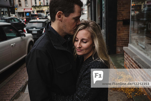Mid adult couple hugging in street