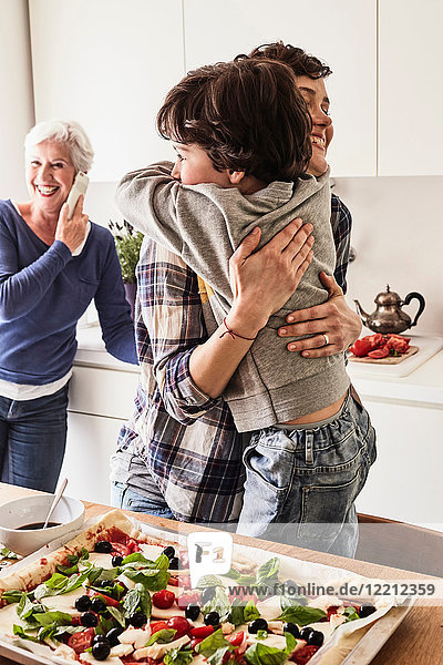Mutter und Sohn umarmen sich in der Küche  Großmutter im Hintergrund mit Smartphone