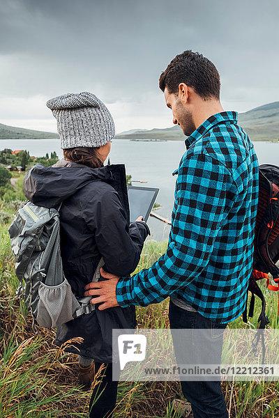 Paar  das neben dem Dillon-Reservoir steht und ein digitales Tablett benutzt  Silverthorne  Colorado  USA