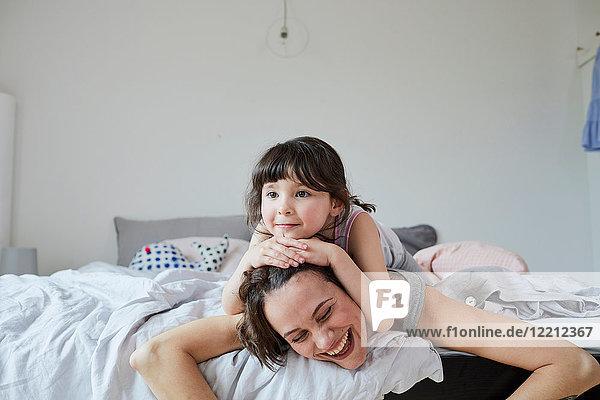 Mutter und Tochter im Bett  Tochter auf dem Rücken der Mutter liegend