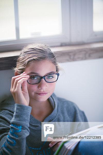 Girl sitting on floor doing homework  portrait