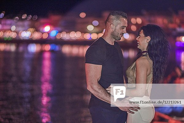 Couple enjoying togetherness in city lights at night. Greek ethnicity. In Hersonissos  Crete  Greece.