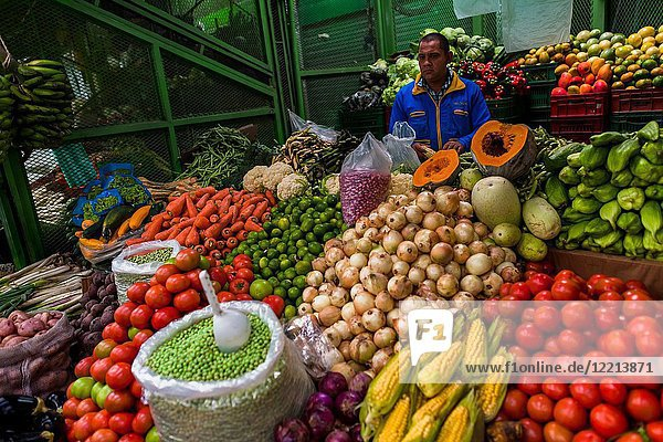 A Colombian vendor  holding a corn  stands behind the piles of vegetables at the market of Paloquemao in Bogotá  Colombia.