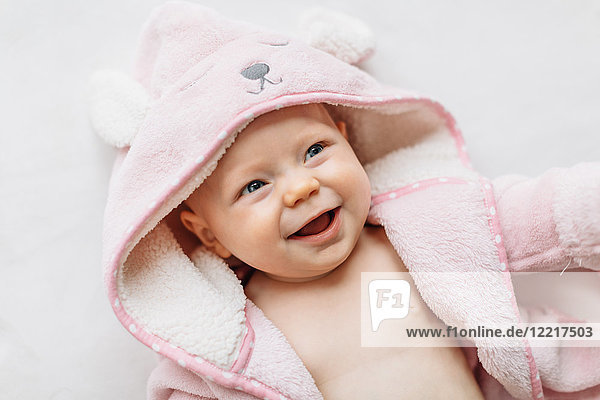 Portrait of baby girl in hooded towel looking away smiling