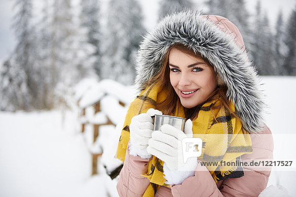 Junge Frau trinkt im Winter Kaffee im Freien