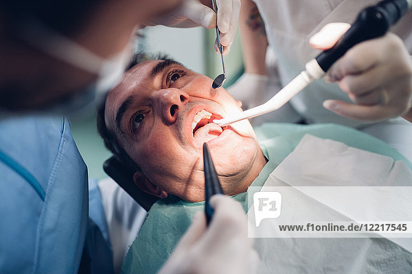 Zahnarzt schaut in den Mund eines männlichen Patienten  Ansicht von oben