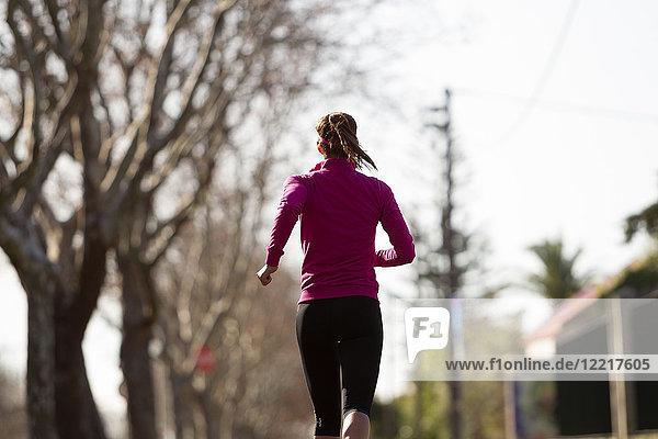 Rückansicht einer jungen Frau beim Joggen
