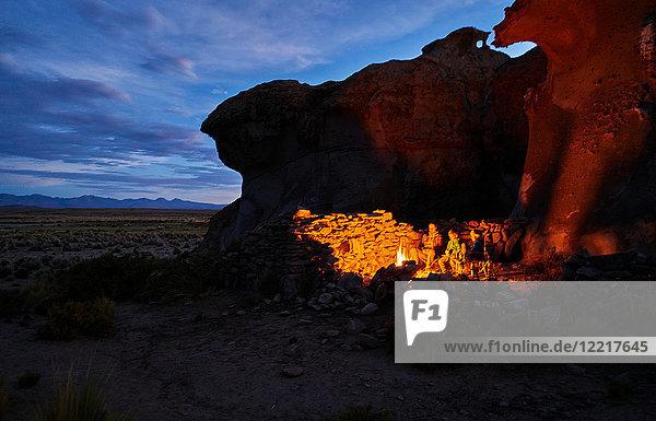 Mutter und Söhne  die in der Abenddämmerung am Lagerfeuer sitzen  Oruro  Oruro  Bolivien  Südamerika