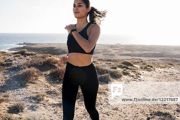Junge Läuferin läuft in trockener Küstenlandschaft  Las Palmas  Kanarische Inseln  Spanien