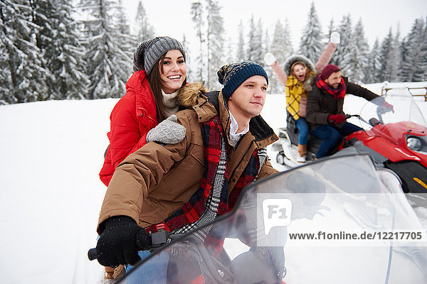 Friends riding snowmobiles in winter