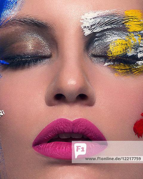 Studioporträt einer Frau mit geschlossenen Augen und abstrakt gemaltem Gesicht  Nahaufnahme