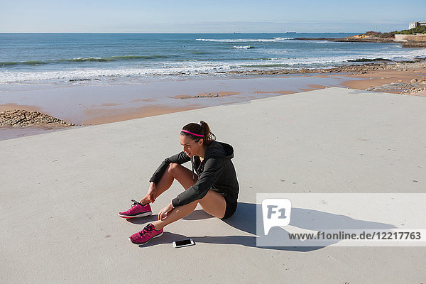 Junge Frau sitzt am Strand  Carcavelos  Lissabon  Portugal  Europa